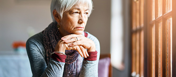 Senior woman rests her chin on her hands while sitting alone looking out the window.