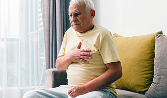 Senior male sitting on a couch at home holds chest after experiencing GERD.