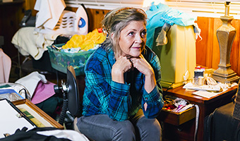 Senior female is depressed sitting in a cluttered room due to a hoarding.