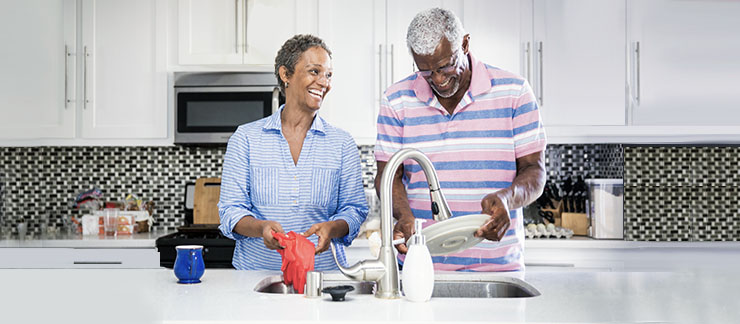 Senior couple sharing housekeeping duties while washing dishes in the kitchen.