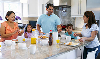 Multigenerational family having breakfast together in the kitchen.
