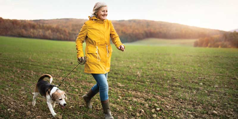 Woman in rainjacket walking dog.