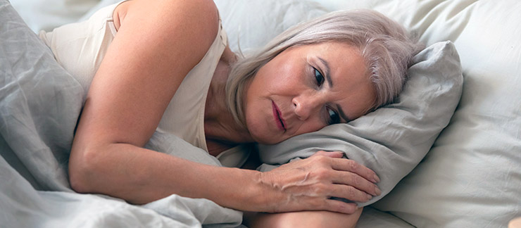 Senior woman lays her head on pillow in bed trying to go to sleep.