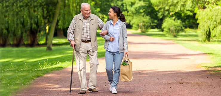 Senior man with can holds arm of female caregiver holding bag of groceries during walk home.