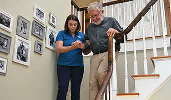 A Visiting Angels care provider helps a man with can to safely walk down the stairs inside his home.