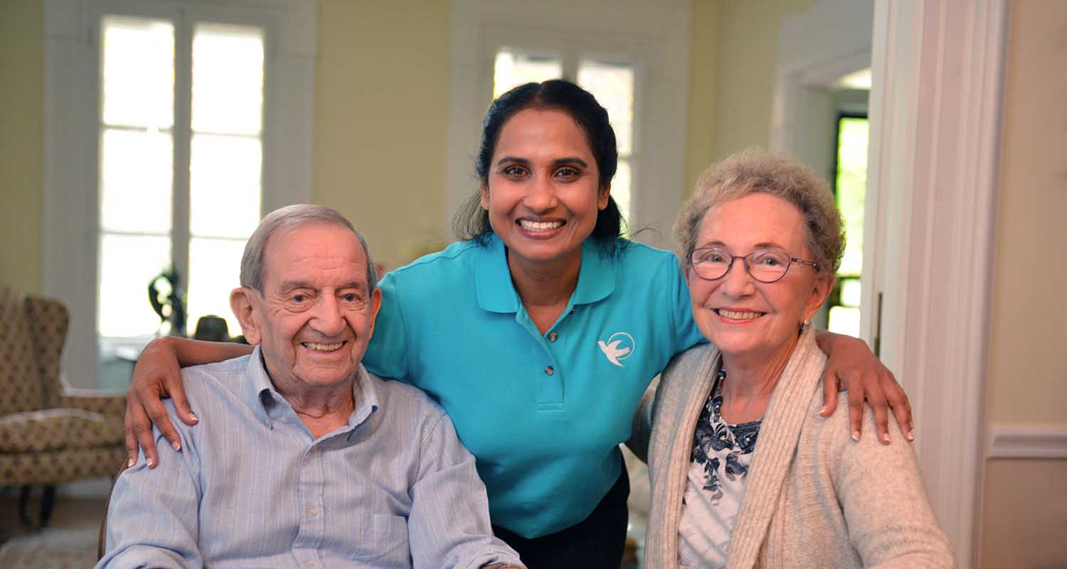 Middle age woman provides senior home care to an elderly couple.