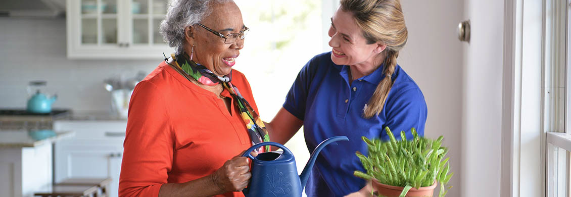 Mid-aged woman takes pride in her caregiver job by helping an elderly woman at home water a plant.