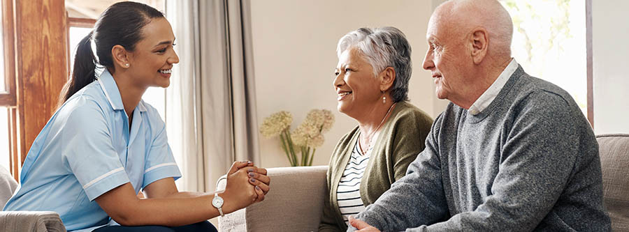 Female caregiver chats with a senior couple at home sitting on sofa
